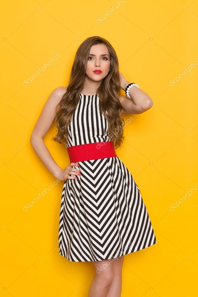 aad47c6e4610d7 Красива молода жінка в чорно-білих Смугасте плаття позують з боку, на  стегні. Три чверті довжина студії розстріляні на жовтому фоні — Фото від  studioloco