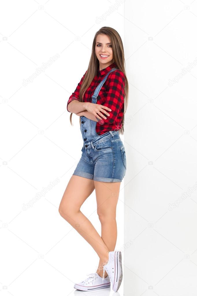 caacd0bcf053f6 Kobieta w drwal czerwona koszula, spodenki jeans spodnie ogrodniczki i  białe trampki pochyla się na biały sztandar. Pełna długość studio strzał na  białym ...