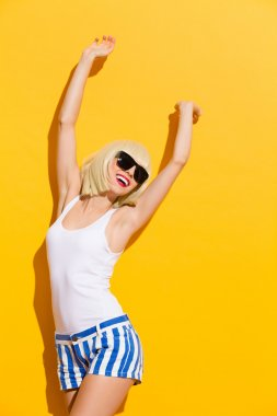 Happy blonde girl in black sunglasses with arms raised
