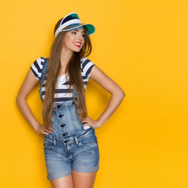 Beautiful Girl In Dungarees And Plastic Sun Visor