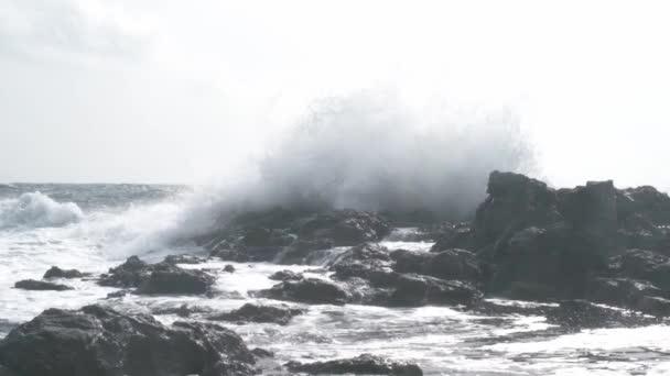 Scénická pobřežní jednotka. Mocná oceánská vlna šplouchá na velkou skálu uprostřed rozbouřeného moře. SLOW MOTION 240 FPS