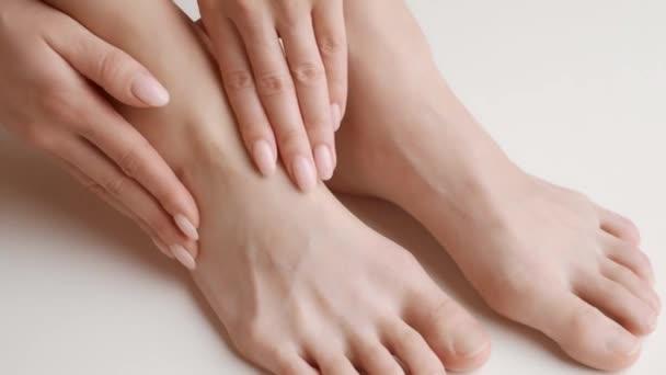 Neznámá žena si masíruje poraněnou nohu, bolest a vymknutí kotníku, zblízka.