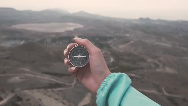 Traveler explorer woman searching direction with a compass in a hand in front of mountain valley and lake. Point of view in first person.
