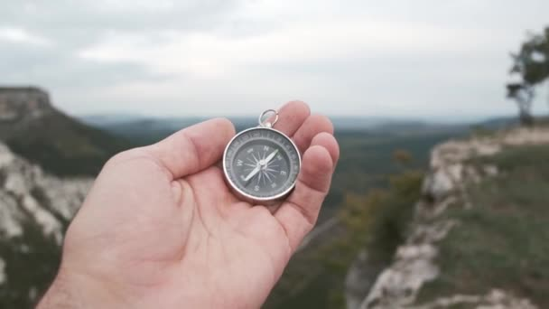 Traveler explorer young man searching direction with a compass in summer mountains, point of view in first person. Hiking. Orienteering on terrain.