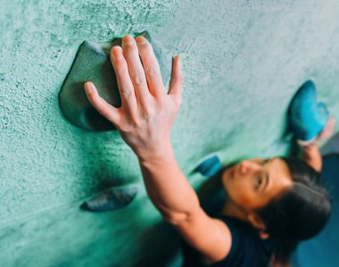 Woman climbing up wall