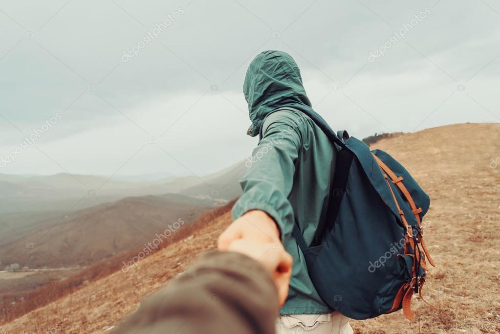 Traveler man holding female hand