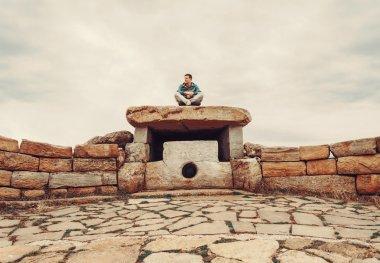 Traveler man sitting on stone dolmen