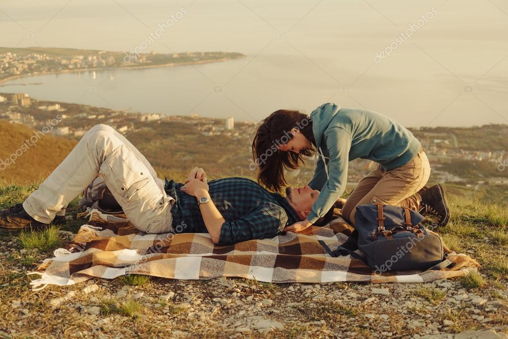 Loving couple resting on peak of mountain