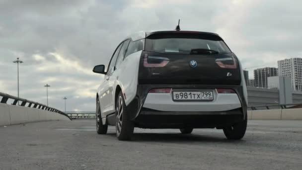 Moskva, Rusko - CIRCA 2020: Elektrický vůz BMW i3 stojí na silnici na pozadí krásné modré oblohy před deštěm. Pohled na kinematografii