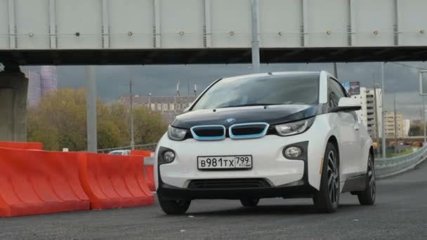 Moskva, Rusko - CIRCA 2020: Elektrický vůz BMW i3 stojí na silnici na pozadí krásné modré oblohy a mostu. Pohled na kinematografii