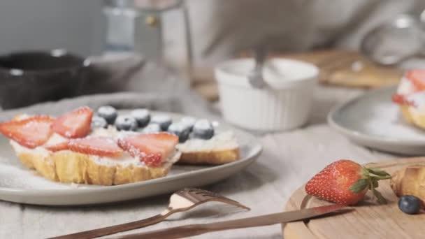 koncept lahodné a vegetariánské snídaně. Croissant nakrájený na polovinu smetanou nebo měkkým sýrem, zdobený borůvkami a jahodami, leží ráno na stole a je připraven ke konzumaci.