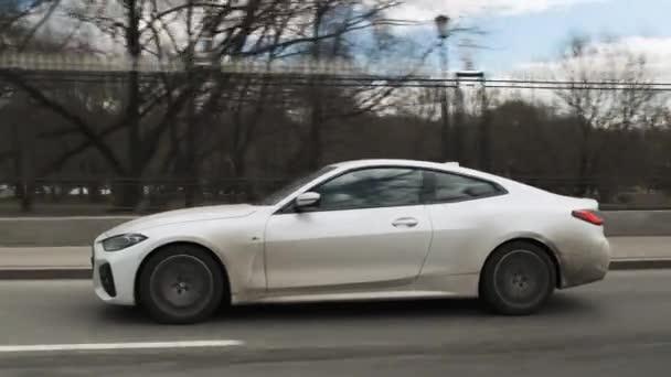 Moskva, Rusko - CIRCA 2021: Nový model BMW 420d 4. model na silnici. Bílé špinavé kupé ve městě. Boční záběry jízdy automobilem na ulici.