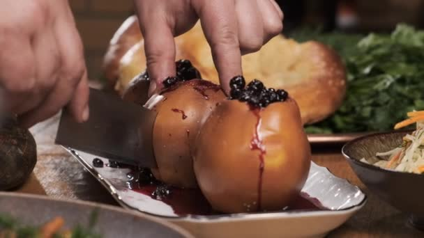 Cooking baked dish. Close up baked apples or quince, from which middle has been cut, is poured with red currant jam. chef prepares dessert and cut in half.