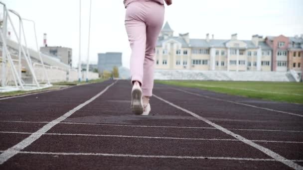fit kavkazský mladý žena běžec v růžové sportovní oblečení běží na stadionu