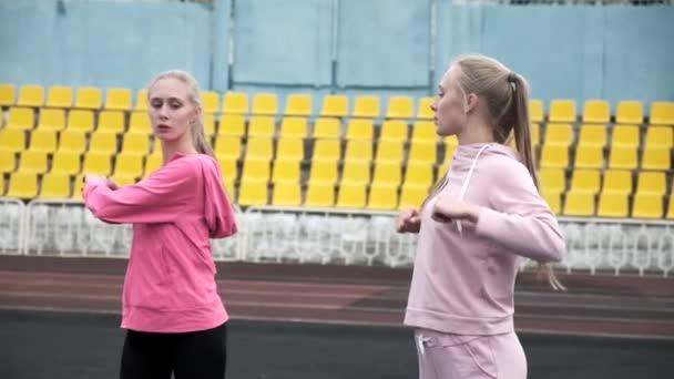 mladá kavkazská identická dvojčata ve sportovním oblečení roztahují svá těla na stadionu