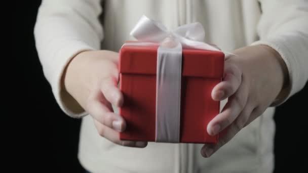 detailní záběr na ruce malé holčičky dávající červenou krabici s bílou stuhou. zimní prázdniny, Vánoce, Nový rok, překvapení. malé dítě dává dárek v krabici na černém pozadí. Osoba drží dárek k narozeninám