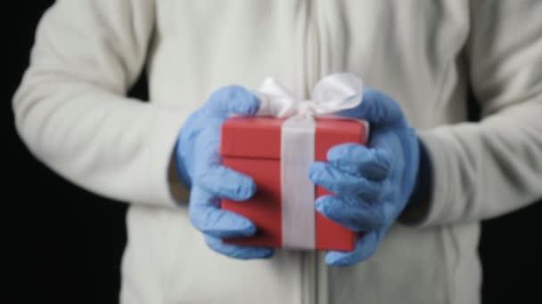malé holčičky ruce v modrých ochranných rukavicích dávat dárkové krabice s bílou stuhou