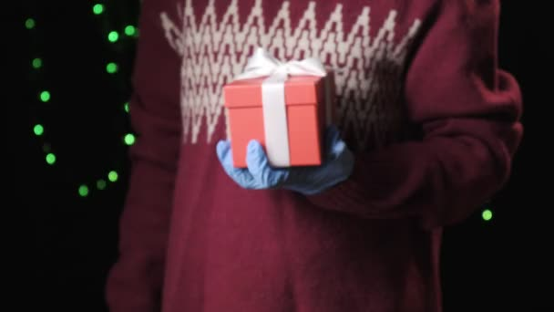 kleine Mädchen Hand in blauen Schutzhandschuhen geben Geschenk-Box mit weißer Schleife