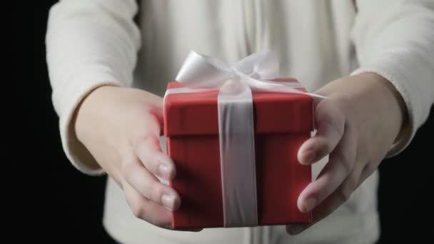 Malé holčičky dávají červené dárkové krabičky s bílou stuhou. Vánoce, Nový rok