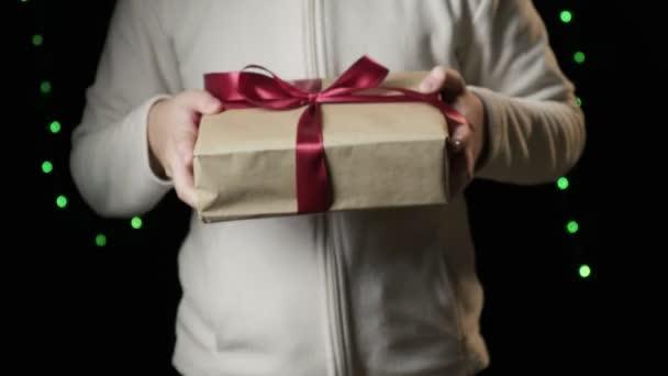 Ckoseup na childs ruce dávat krabici s červenou stuhou. Vánoce, novoroční koncept