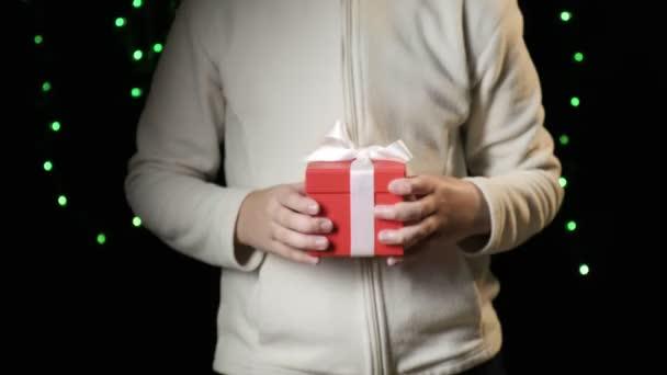 childs ruce dávat červenou krabici s bílou stuhou. Vánoce, novoroční koncept