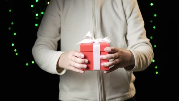 Kinderhände überreichen rote Schachtel mit weißer Schleife. Weihnachten, Neujahrskonzept