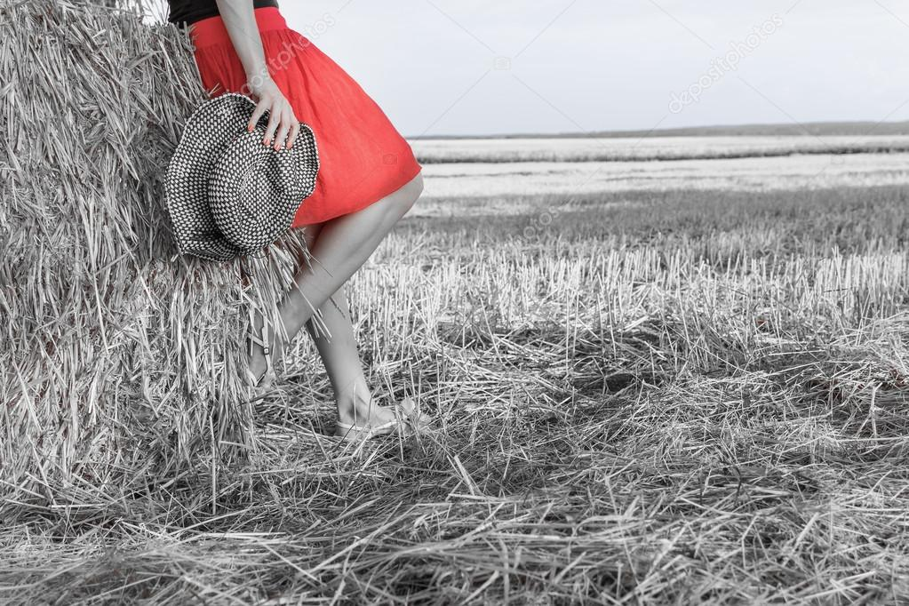 Dettaglio delle gambe di donna e cappello contadino nel campo della paglia–  immagine stock 564a80391924