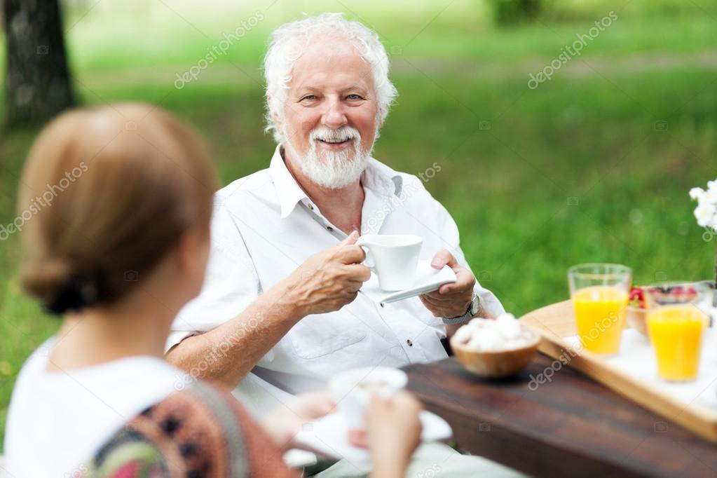 Senior couple enjoying cup of coffee outdoors
