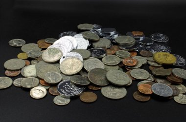dirty old coins on a black background