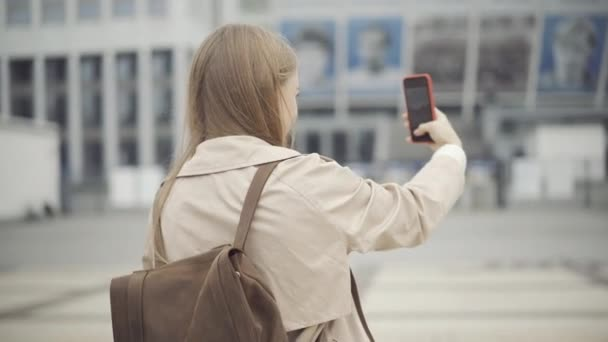 Young female tourist taking photos of foreign city on cloudy spring or autumn day. Beautiful slim Caucasian woman using smartphone to photograph sights abroad. Tourism and travelling concept.