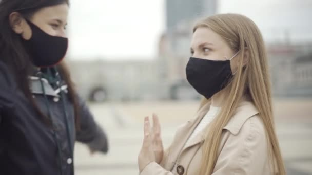 Close-up of young woman in Covid face mask stopping friend from hugging. Portrait of serious Caucasian friends meeting on city square during coronavirus viral pandemic lockdown.