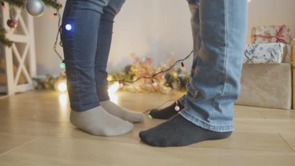 Felismerhetetlen férfi és nő lábai állnak otthon karácsonyi koszorúval. A feleség lábujjhegyen áll, hogy megcsókolja a férjét szilveszterkor. Téli ünnepek.