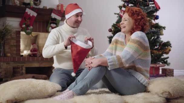 Radostný běloch si nasazuje vánoční klobouk na hlavu usměvavé veselé ženy. Pozitivní pár baví doma na Silvestra. Vánoční oslavy a radost.