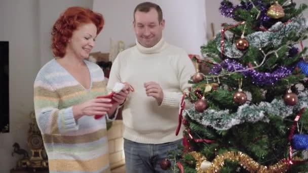 Boldog fehér felnőtt pár díszíti karácsonyfát otthon szilveszterkor. Az örömteli mosolygó férfi és nő portréja, amint a fenyőfára akasztják a kesztyűt. Vidám házastársak teleportáló ház.