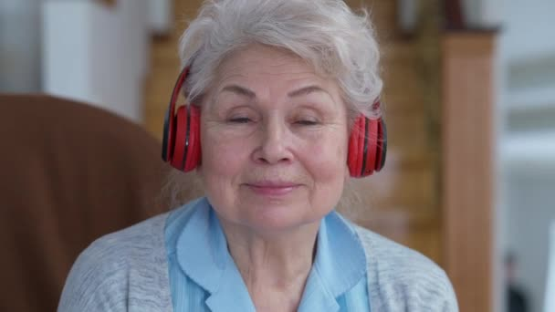 Headshot of joyful carefree senior woman in headphones looking at camera dancing to music. Close-up portrait of cheerful relaxed Caucasian retiree enjoying hobby at home indoors smiling.