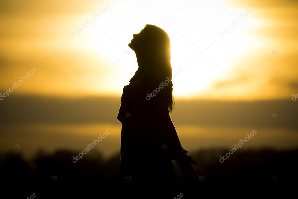 Twilight silhouette by beautiful sunny young woman in summer