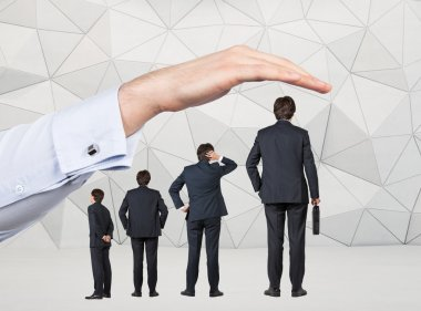 Four businessmen of different size arranged by tallness standing under a huge hand. Grey geometric background. Concept of career growth. stock vector