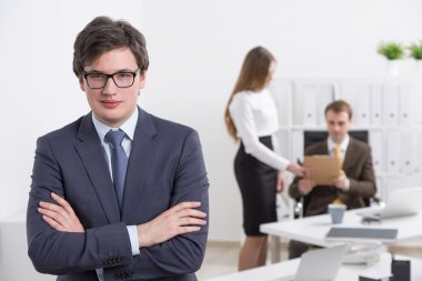 Young businessman with crossed hands, two colleagues at background. Concept of team work.