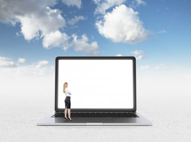 Businesswoman standing in front of huge blank laptop screen. Side view. Blue sky at background. Concept of expectations.