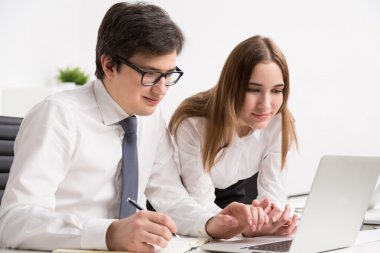 Young smiling businessman looking at laptop screen and making notes, businesswoman next to him. Concept of help.