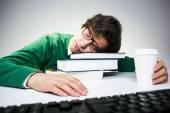 Mladý student v zelený svetr spí na stole s knihy, coffee cup a počítačové klávesnice