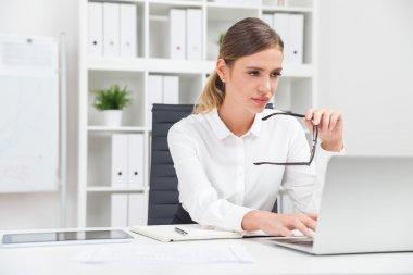 Woman typing at laptop keyboard