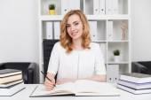 Gefeierte Autorin, die ihr neues Buch im Büro mit Bücherregal schreibt. Konzept der kreativen Arbeit und ihre Herausforderungen