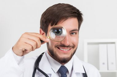 Close up of smiling doctor with magnifying glass