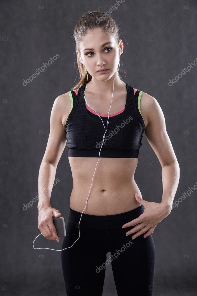 d33068d161c Фитнес-тренер готовится для класса с наушниками и смарт-телефон стоял у  серой стены в ее спортивной одежде. Концепция движения-это жизнь — Фото  автора ...