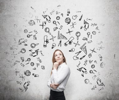 Young beautiful business woman is thinking about optimisation business process. Drawn business icons over the concrete wall.