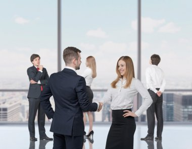 Happy young professionals are standing in a contemporary glass office in New York. Handshake as a concept of successful decision making process.