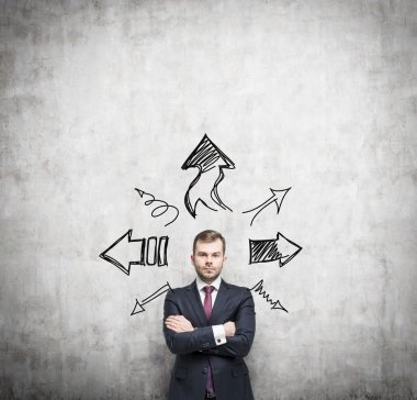 Businessman is standing surrounded by arrows in different direction. A concept of decision making process. Concrete wall background.