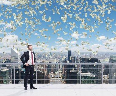 Confident handsome businessman is standing on the roof terrace in New York City. Falling dollar notes from the sky. A concept of financial consultancy.
