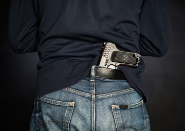 Hided handgun under the denim belt.